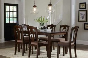 dinning room table with flower vase in center and surrounded by six chairs