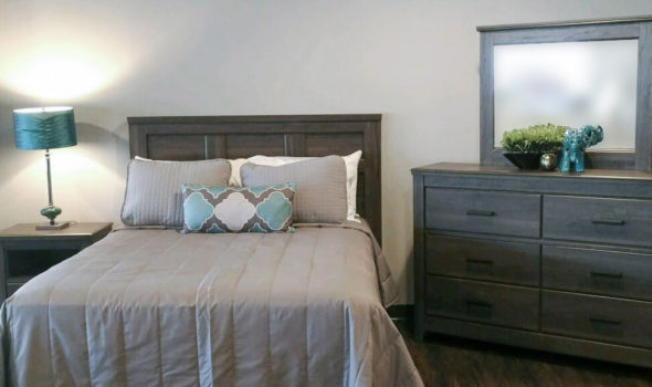 Bedroom setting with bed and dresser with mirror