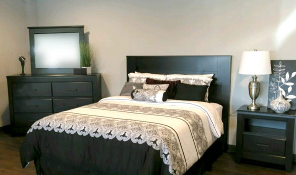 Bedroom setting with bed, bedside table and dresser with mirror