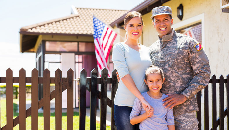 Military family posing outside of their home with american flag flying in background